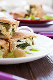 Egg-spinach pie cut into pieces on white dish Stock Images