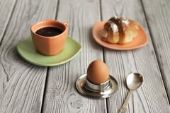 English breakfast, coffee with egg and croissant. Egg in a stand, coffee and croissant in the background, close-up on a wooden background Royalty Free Stock Photo