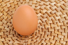 Egg standing on bamboo placemat Stock Image