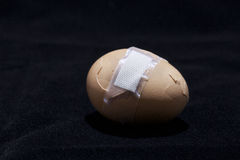 Egg with sticking plaster Stock Photos