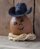 Egg su un nido stilizzato su un bordo di legno 3 Fotografia Stock