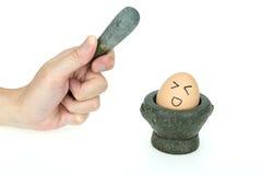 Egg sul mini mortaio della cucina, impaurito di ottenere lo schiacciamento, su fondo bianco Fotografie Stock Libere da Diritti