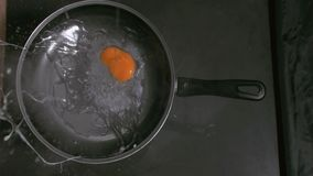 Egg in super slow motion falling in a pan Royalty Free Stock Photo