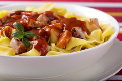 Egg tagliatelle. With meat in tomato sauce Stock Images