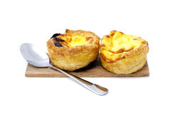 Egg tart couple on wood plate with stainless steel spoon. Isolated white background Royalty Free Stock Image
