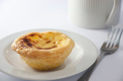 Egg tart with morning coffee. A chinese egg tart with a cup of coffee in the background Stock Photography