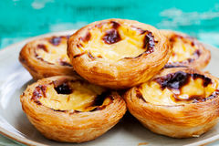 Egg tart Portuguese dessert, pastel de nata. Egg tart, traditional Portuguese dessert, pastel de nata on a plate. Colorful wooden background Royalty Free Stock Photo