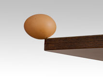 Egg teetering on the edge. Brink. Royalty Free Stock Images