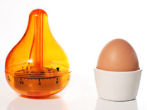 Egg Timer next to Egg in Cup. An orange egg timer next to an egg in a white cup Royalty Free Stock Photography