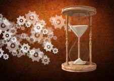 Egg Timer with sand and cog wheel settings icons against brown background Royalty Free Stock Photo