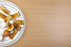 Egg and toasted soldiers on a white pattened plate Royalty Free Stock Photos