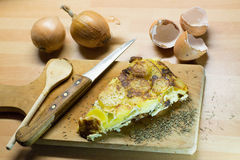 Egg tortilla on cutting board. Overhead shot of slice of egg tortilla on cutting board with knife, wooden spoon and herbs on wooden tabletop with egg shells and Royalty Free Stock Photography