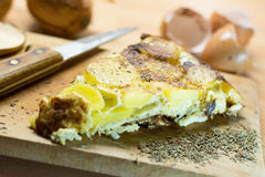Egg tortilla. Slice of tortilla de patata, or egg tortilla, on wooden cutting board with knife and herbs Stock Images
