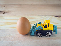 Egg with toys car on wood floor. Bussiness concept Stock Images