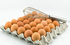 Egg tray and hand whisk Royalty Free Stock Image