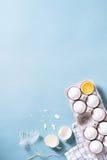 Egg, un huevo agrietado con una cáscara de huevo, yema de huevo y clara de huevo Cocinar el fondo de la turquesa de la comida Vis Imagen de archivo
