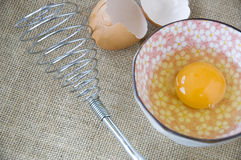 Egg whisk with uncooked egg Royalty Free Stock Photography