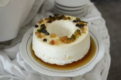 egg white pudding with sugar syrup and dried fruit on an ornate round dish stock photo