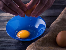 Egg on a wooden table. Egg in a blue plate on a wooden table illuminated side light Stock Photography