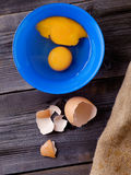 Egg on a wooden table. Egg in a blue plate on a wooden table illuminated side light Royalty Free Stock Photos
