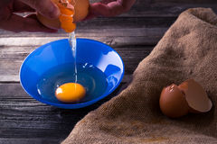 Egg on a wooden table. Egg in a blue plate on a wooden table illuminated side light Royalty Free Stock Photo