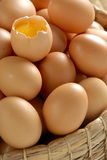 Egg yolk. On pile of eggs, in a basket Stock Photography