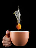Egg Yolk dripping in to cup. Royalty Free Stock Photography