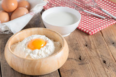 Egg yolk in the flour with milk and whip for beating on wood tab Stock Images