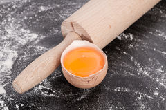 Egg yolk with rolling pin. Baking background with flour, ingredients, rolling pin, making  dough and  pastry, homemade, preparation, recipe utensils,egg yolk Royalty Free Stock Photo