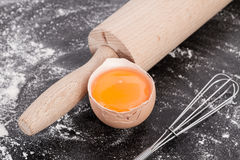 Egg yolk with rolling pin close up. Baking background with flour, ingredients, rolling pin, making  dough and  pastry, homemade, preparation, recipe utensils,egg Stock Images