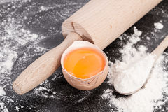 Egg yolk with rolling pin and flour. Baking background with flour, ingredients, rolling pin, making  dough and  pastry, homemade, preparation, recipe utensils Royalty Free Stock Photos