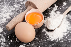 Egg yolk with rolling pin and flour. On black background, baking and making dough, homemade, baking ingredients on dark background Royalty Free Stock Photography