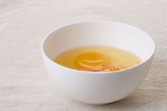 Egg yolk. In white bowl on table, closeup stock images