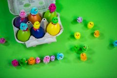 Eggbox with eggs and funny chicks, green background. Postcard Royalty Free Stock Photos