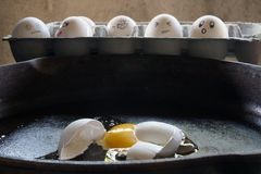 The Eggcident. Horrified eggs see another egg break in a frying pan Royalty Free Stock Photos