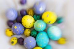 Egge amarillo, violeta, azul y verde de Pascua con los dibujos tenidos de las mariposas, lunares, espirales Imagen de archivo
