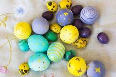 Egge giallo, viola, blu e verde di Pasqua con i disegni avuti delle farfalle Fotografia Stock