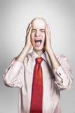 Egghead guy in suite screams. Stock Photos