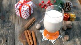 Eggnog напитка домодельного традиционного рождества подготовки пряный горячий с земным мускатом, циннамоном в стекле, сток-видео