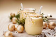 Eggnog alcoholic beverage served with cinnamon or nutmeg.  Traditional drink often served during Christmas Stock Photos