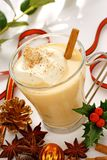 Eggnog at christmas time. Eggnog in a glass at christmas time Stock Images