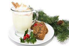 Eggnog with Fruitcake. Holiday eggnog with fruitcake, isolated on white with holly and pine garnish Royalty Free Stock Photo