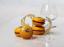 Eggnog macarons. With golden ribbons, diamonds and cognac glasses Stock Images