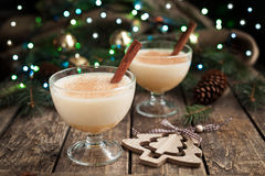 Eggnog traditional xmas homemade winter egg, milk. Rum, vanilla alcohol liqueur preparation recipe in two glass cups with cinnamon sticks on wooden vintage Royalty Free Stock Photos