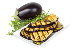 Eggplant. Grilled eggplant slices on a plate, with whole eggplant and fresh rosemary and oregano Stock Images