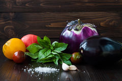 Eggplant (aubergine) with basil, garlic and tomatoes on dark wooden table. Fresh raw farm vegetables - harvest from the. Garden in rustic kitchen. Rural still Stock Images