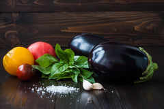 Eggplant (aubergine) with basil, garlic and tomatoes on dark wooden table. Fresh raw farm vegetables - harvest from the. Garden in rustic kitchen. Rural still Royalty Free Stock Photography