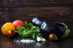Eggplant (aubergine) with basil, garlic and tomatoes on dark wooden table. Fresh raw farm vegetables - harvest from the. Garden in rustic kitchen. Rural still Stock Photography