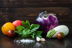 Eggplant (aubergine) with basil, garlic and tomatoes on dark wooden table. Fresh raw farm vegetables - harvest from the. Purple and white eggplant (aubergine) Royalty Free Stock Images