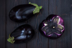 Eggplant (aubergine) on dark wooden table. Top view. Fresh raw farm vegetables - harvest from the garden in rustic kitch. En. Rural still life from above Royalty Free Stock Images